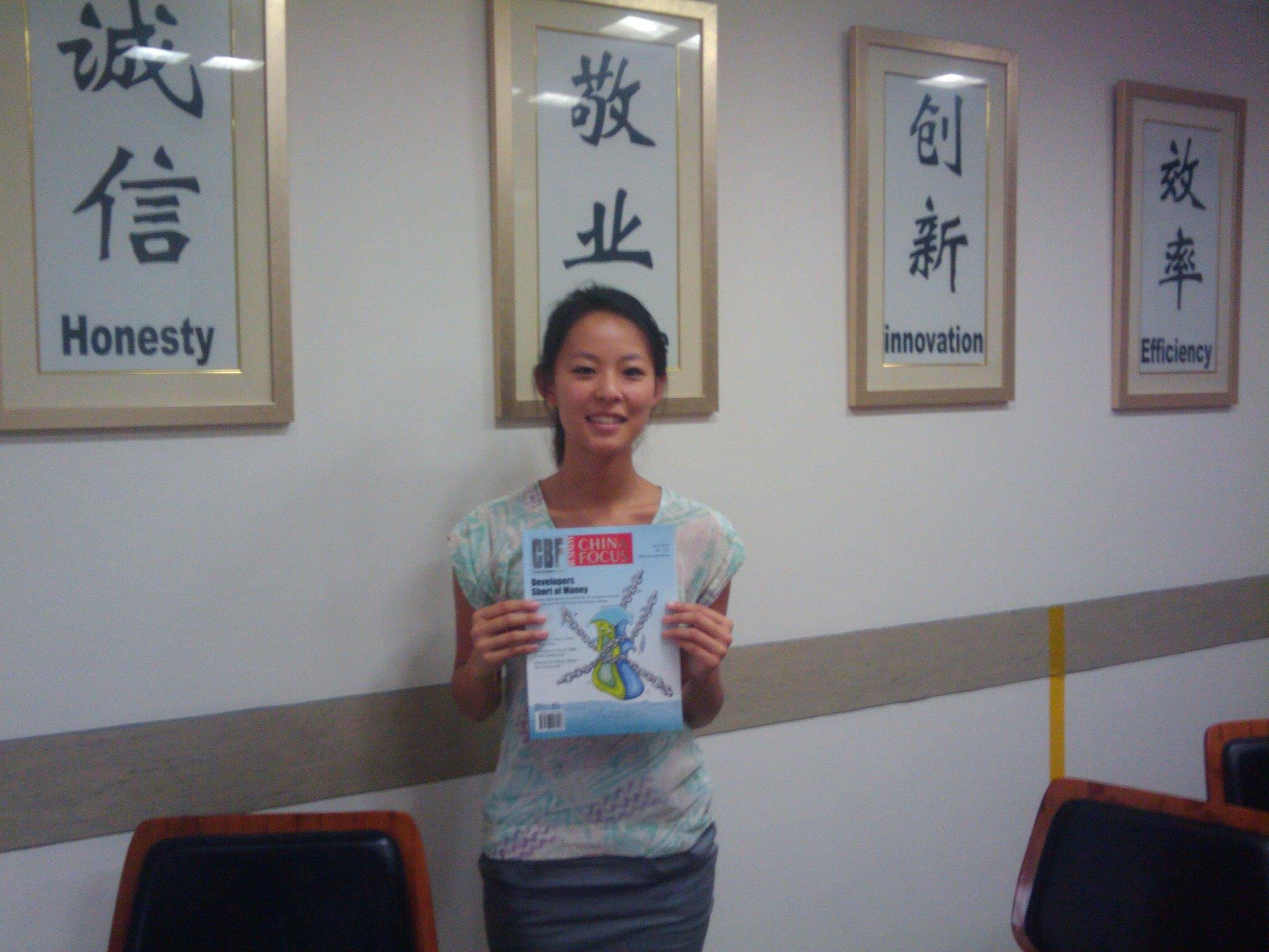 An intern in China takes a picture with a magazine at her placement